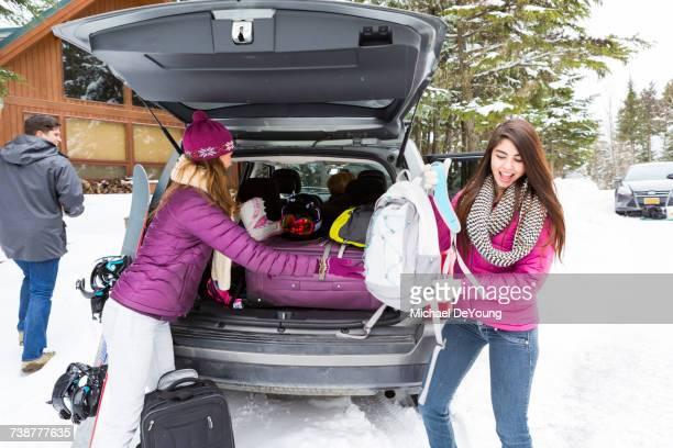 Friends unloading car at winter resort