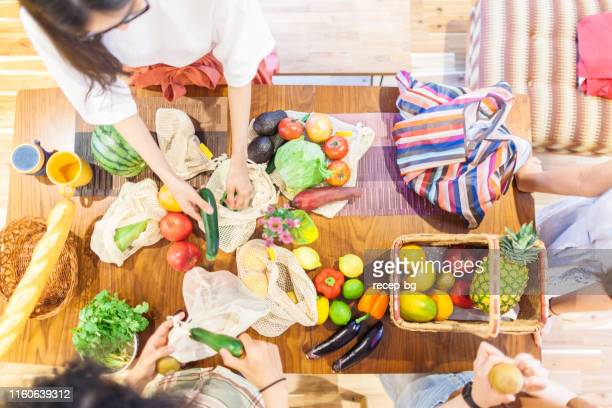 friends unpacking their reusable shopping bags after shopping at supermarket for home party - kitchen after party stock pictures, royalty-free photos & images