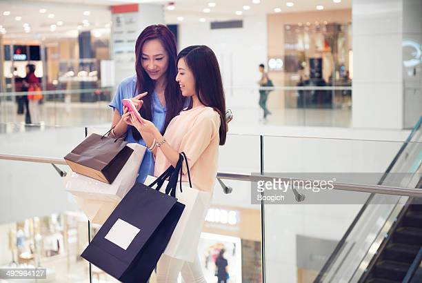 friends update social media status in hong kong luxury mall - fashion hong kong stock photos and pictures