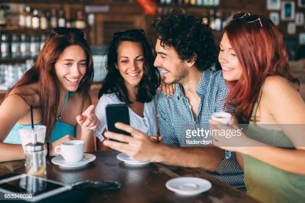Vrienden met behulp van een slimme telefoon in het café