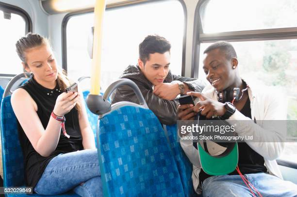Friends using cell phones on bus
