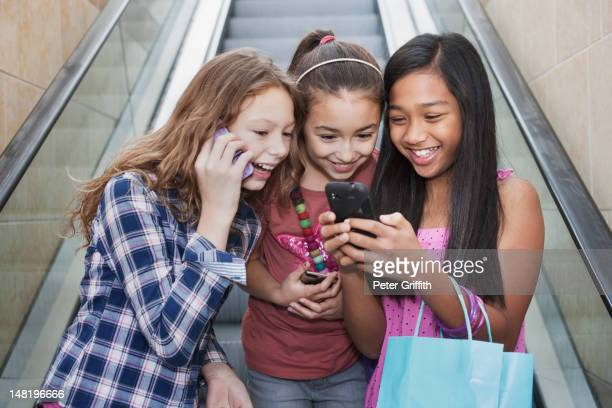 Friends using cell phones on shopping mall escalator