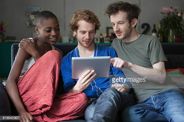 friends using digital tablet together on sofa at home - seulement des adultes photos et images de collection