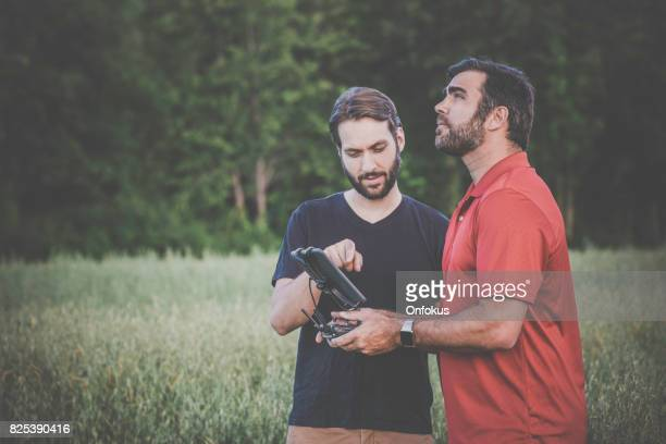 Friends Using Drone Controlled by Digital Tablet Outdoor