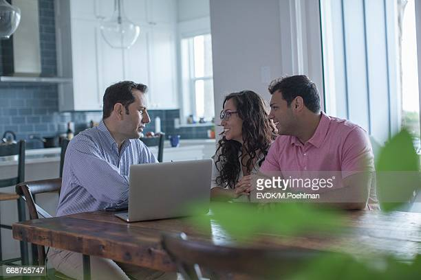 Friends using laptop and talking in kitchen