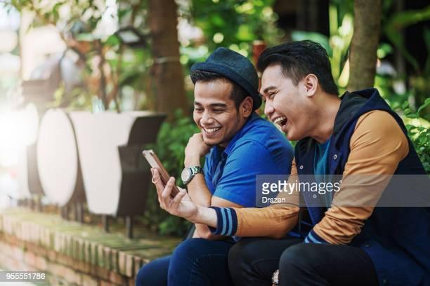 amigos, usando o aplicativo móvel em smartphone - malásia - fotografias e filmes do acervo