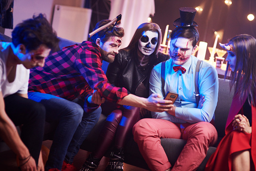 Friends using mobile phone at Halloween party - gettyimageskorea