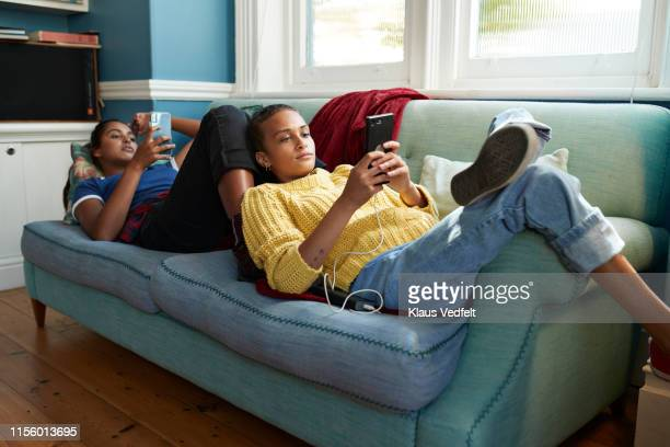 friends using mobile phones while lying on sofa - roommate stock pictures, royalty-free photos & images