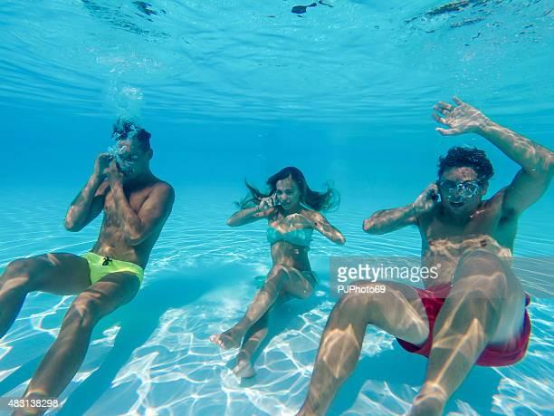 Friends using smart phone underwater