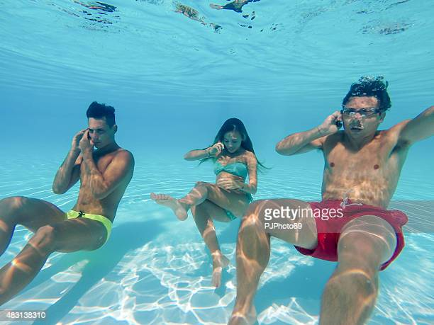 Friends using smart phone underwater