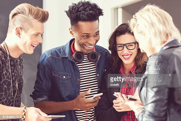 Amigos utilizando teléfonos inteligentes en el interior