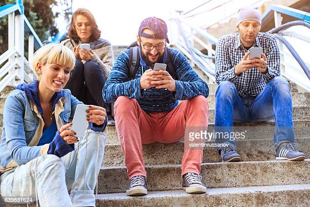 Friends using smart phones on stairs