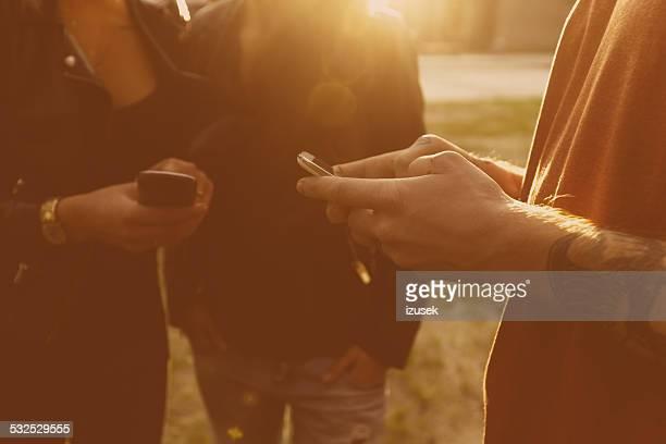 Friends using smart phones outdoor