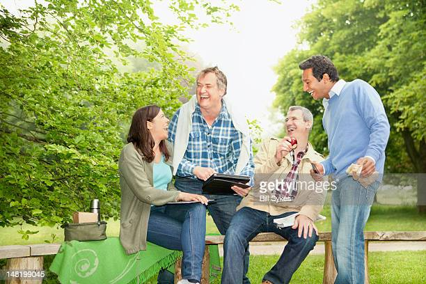 Friends using tablet computer in park