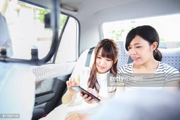 日本でタクシーを使用し、観光名所を探索する彼らのスマート フォンを使用しての友人