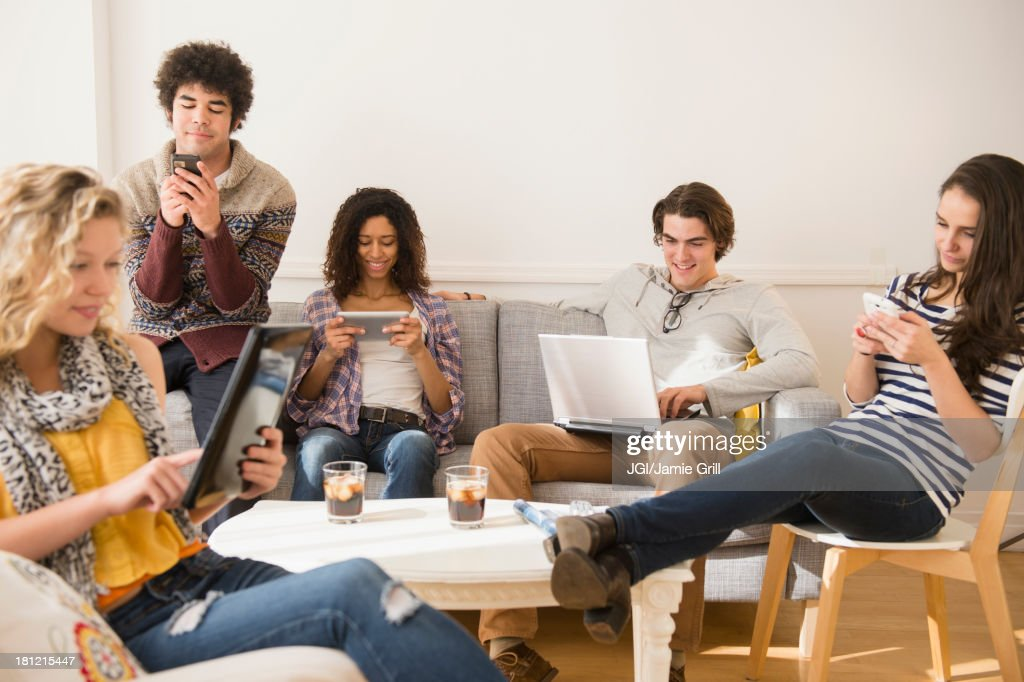 Friends using technology in living room : Stock Photo