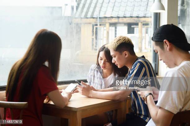 friends using their phones in a cafe - filipino ethnicity and female not male stock pictures, royalty-free photos & images