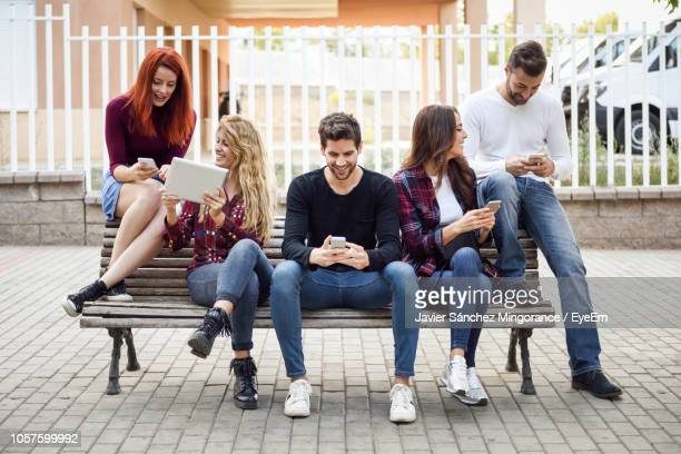 friends using various technologies while sitting on bench in city - bench stock pictures, royalty-free photos & images