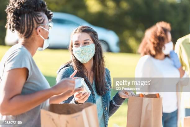 des amis font du bénévolat à la banque alimentaire pendant la crise covide-19 - gratuit photos et images de collection