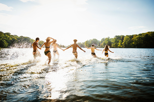 Friends Wading Into Lake In Summer Sun - gettyimageskorea