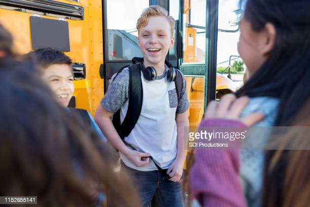 friends wait to load onto bus for field trip - preadolescente foto e immagini stock