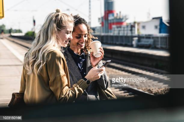 friends waiting at train station looking at smartphone - railroad station stock pictures, royalty-free photos & images