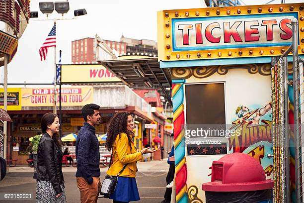 friends waiting in line at amusement park ticket booth - traveling carnival stock pictures, royalty-free photos & images
