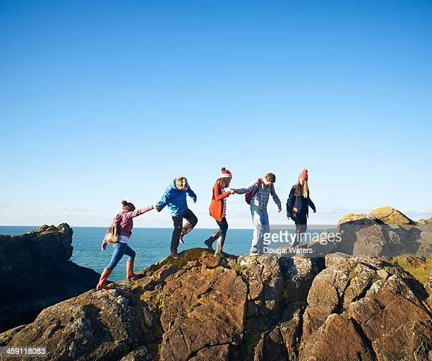 Friends walk along coastal rocks.