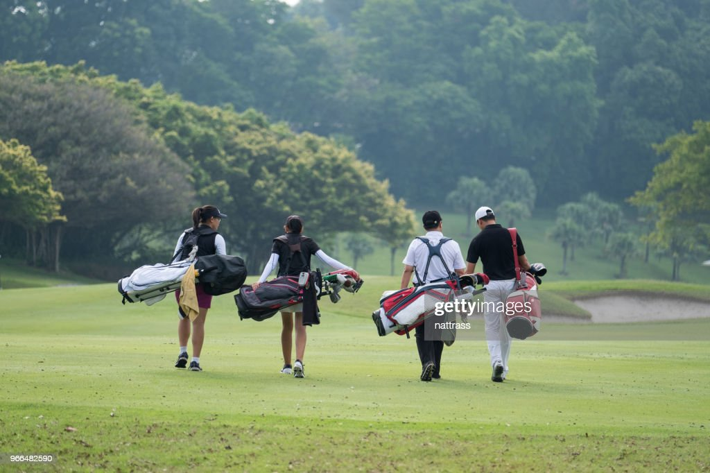 Friends walk together down the fairway : Stock Photo