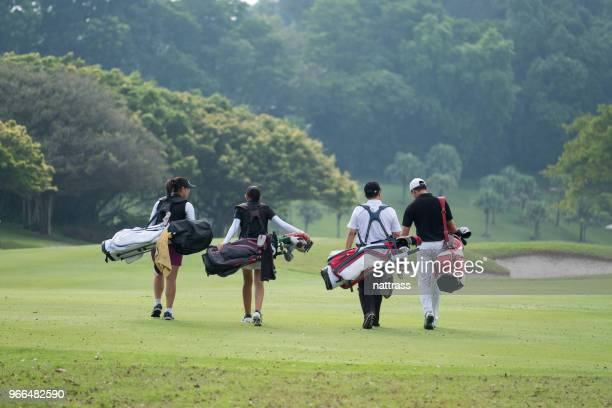 friends walk together down the fairway - golf stock pictures, royalty-free photos & images