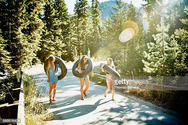 Friends walking across bridge holding inner tubes