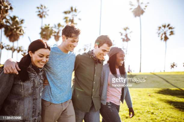 friends walking all together on venice beach - arm in arm stock pictures, royalty-free photos & images
