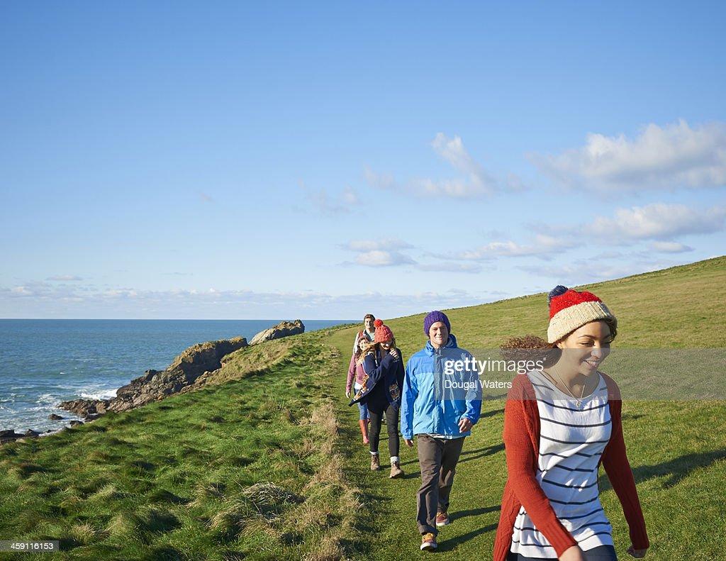 Friends walking along coastal path. : Stock Photo