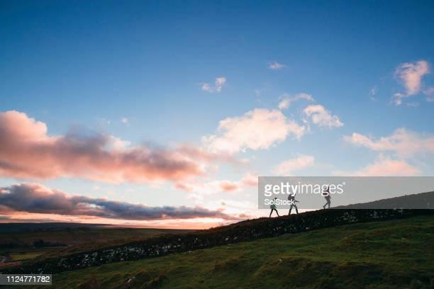 vrienden wandelen langs de muur van hadrianus - noordoost engeland stockfoto's en -beelden