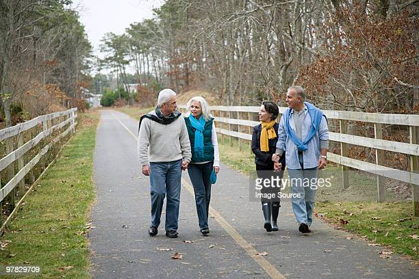 friends walking along path - 50 59 years stock pictures, royalty-free photos & images