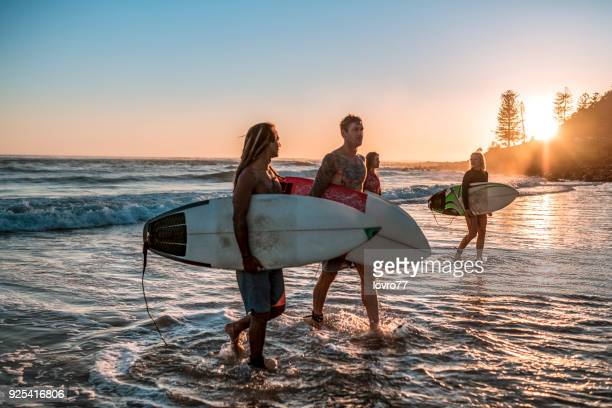 friends walking along the coast with surfboards - gold coast queensland stock pictures, royalty-free photos & images