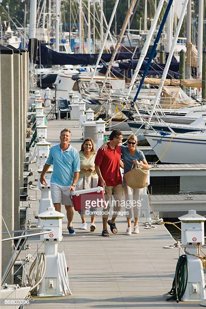 friends walking along yachting pier - marina stock pictures, royalty-free photos & images