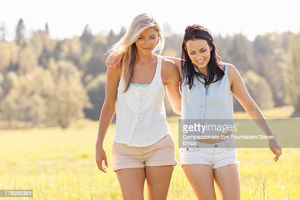 Friends walking arm in arm outdoors