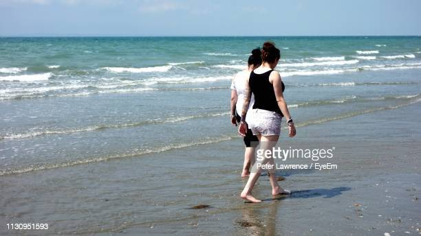 friends walking at beach against sky during sunny day - portsmouth england stock pictures, royalty-free photos & images