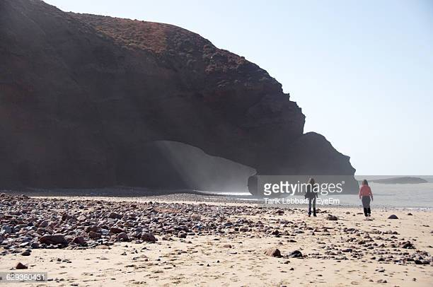 Friends Walking At Beach By Rock Formation Against Clear Sky