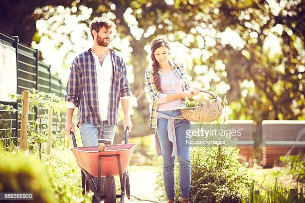 Friends walking at organic farm on sunny day