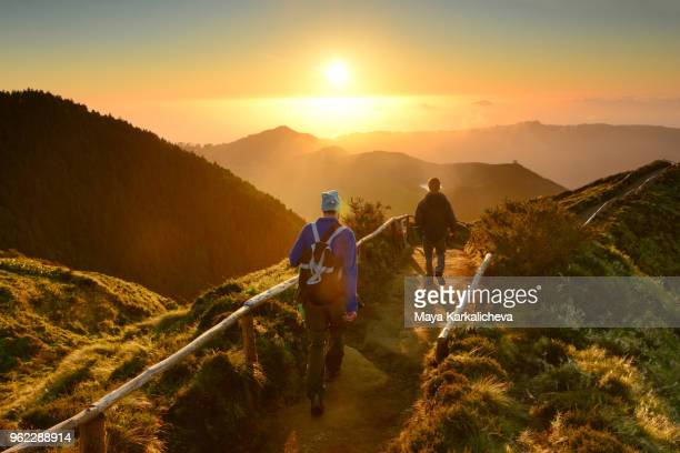 Friends walking at sunset at Sete Cidades lakes, Sao Miguel island, Azores, Atlantic ocean, Portugal
