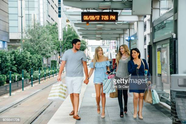 Friends walking at train station carrying shopping bags