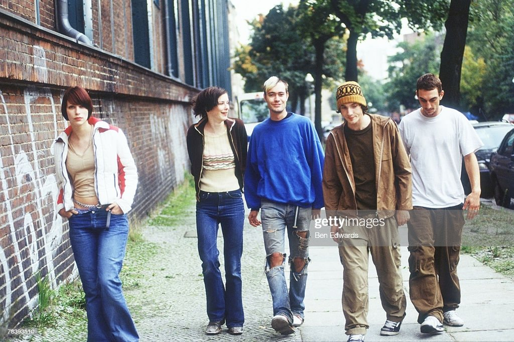 Friends walking down sidewalk : Bildbanksbilder