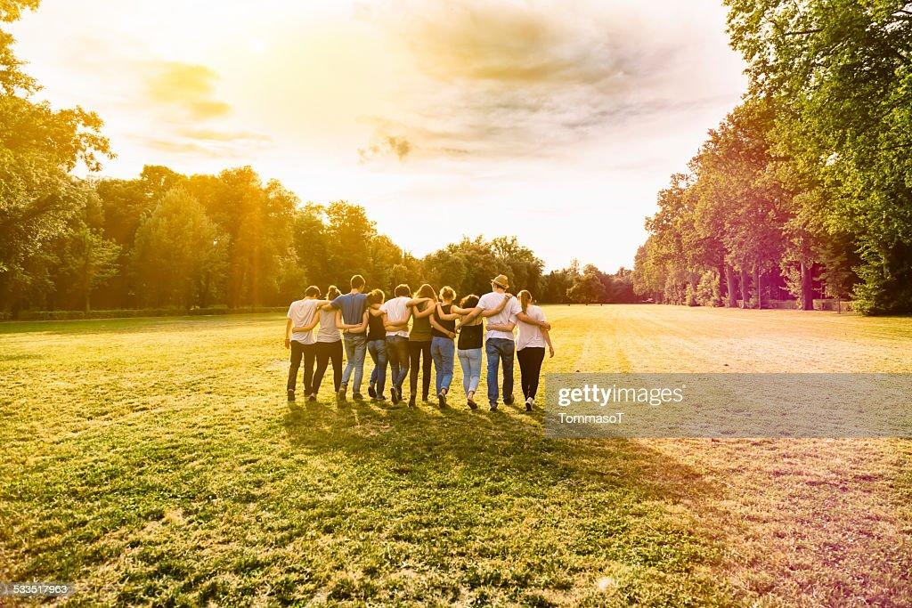 Amigos caminando en un parque, en sunset agarrados del brazo : Foto de stock