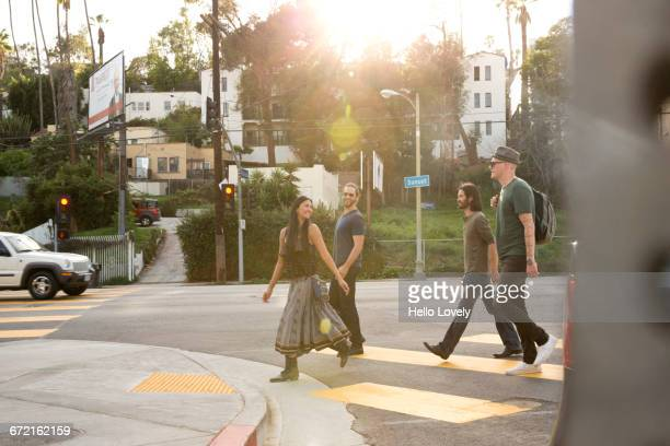 friends walking in city crosswalk - street fair stock photos and pictures