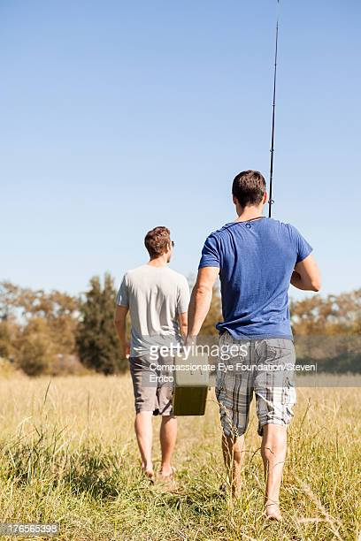 Friends walking in field with fishing rods