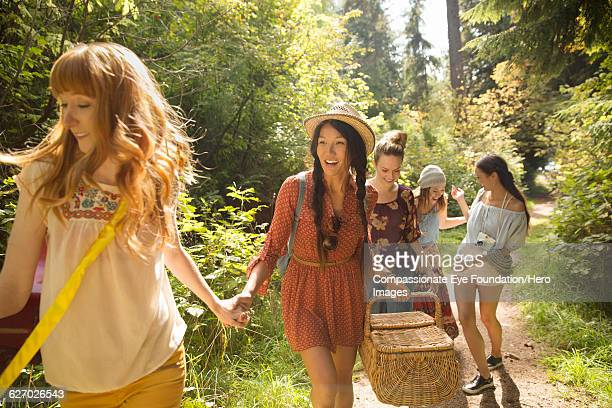 Friends walking in forest with picnic basket