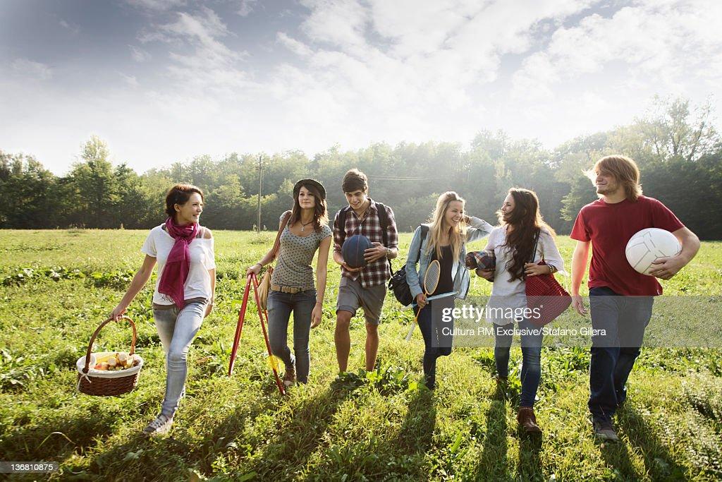 Friends walking in rural field : Stock Photo