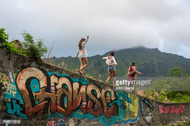Friends walking on graffiti wall near mountain